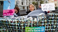 Campaigners attend a protest to protect the critically endangered Maui's dolphin, in front of Parliament House in Wellington on…