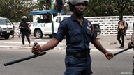 Police officers stand guard as protesters march in Ghana's capital Accra against the expansion of its defence cooperation with…