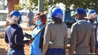 Police arrest a health worker during a protest against economic hardship and poor working conditions during the coronavirus.