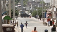 An armoured personnel carrier (APC) is seen on a sealed off street during fighting