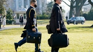 "A U.S. military aide, left, carries the ""President's emergency satchel,"" also know as ""the football,"" with the nuclear launch…"