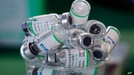 Empty vials of China's Sinopharm vaccine sit in a cup during a priority COVID-19 vaccination campaign of health workers at a…