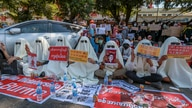 Hooded demonstrators display placards accusing China for supporting Myanmar's military during a protest against the recent coup…