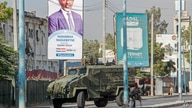 Security forces block a street with an armored personnel carrier during protests against the government and the delay of the…