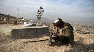 FILE - A man reads the Quran besides his relative's grave in a cemetery on the outskirts of Kabul, Afghanistan, Jan. 14, 2021.