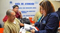 FILE - An immigration officer checks documents of a Salvadoran citizen deported from the U.S., at a Migrants Center in San Salvador, June 22, 2018.