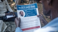 A man holds a flyer printed by the International Criminal Court (ICC) explaining the trial of LRA commander Dominic Ongwen, in Lukodi, Uganda, Feb. 4, 2021.