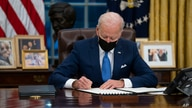 FILE - President Joe Biden signs an executive order, in the Oval Office of the White House, in Washington, Feb. 2, 2021.