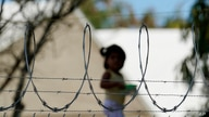 FILE - A child plays at a camp for asylum seekers stuck on America's doorstep, in Matamoros, Mexico, Nov. 18, 2020.