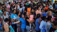 """Migrants, many of whom were returned to Mexico under the Trump administration's """"Remain in Mexico"""" policy, wait in line to get a meal in an encampment near the Gateway International Bridge in Matamoros, Mexio, Aug. 30, 2019."""