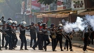 Riot police officers fire teargas canisters during a protest against the military coup in Yangon, Myanmar, Feb. 28, 2021.
