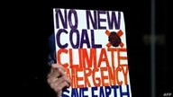 An environmental activist from Extinction Rebellion holds up a placard during a protest against the India-backed Adani coal…