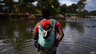 A migrant carrying a baby crosses the Chucunaque river after walking for five days in the Darien Gap, in Bajo Chiquito village,…