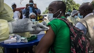 A health worker from the Guinean Ministry of Health cleans a suspected contact of an Ebola patient's arm ahead of administering…