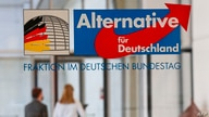 Two persons walk behind the logo of the parliamentary group of the Alternative for Germany (AfD) far-right party  on March 3,…