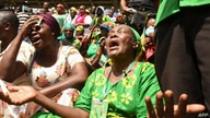 Women cry as attendees mourn the death of the coffin of fifth Tanzanian president John Magufuli during the national funeral at…