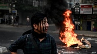 A protester with his face painted stands near a burning makeshift barricade during a protest against the military coup, in…