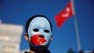 An ethnic Uighur boy wears a mask during a protest against China in Istanbul, Turkey December 14, 2019. REUTERS/Kemal Aslan