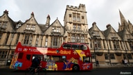 FILE PHOTO: A sightseeing bus passes Oxford University building, amid the spread of the coronavirus disease (COVID-19), in…