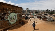 FILE PHOTO: A boy walks in front of a graffiti promoting the fight against the coronavirus disease (COVID-19) in the Mathare…