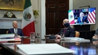 U.S. President Joe Biden and Homeland Security Secretary Alejandro Mayorkas listen during a virtual bilateral meeting with…