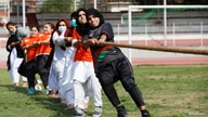 Women participants react as they pull a rope during a sports event in connection with the International Women's Day…