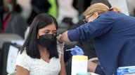 FILE PHOTO: A woman receives a coronavirus disease (COVID-19) vaccination, at Jordan Downs in Los Angeles, California, U.S.,…