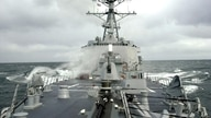 FILE - Sea spray whips across deck of USS Winston Churchill guided missile destroyer (DDG 81).