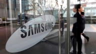 FILE - In this Jan. 31, 2018 file photo, an employee walks past a logo of the Samsung Electronics Co. at its office in Seoul,…