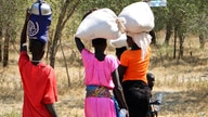 In this photo taken Friday, Dec. 7, 2018, women and girls walk back after getting food in Bentiu, a 38 kilometers (24 miles)…