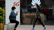 A woman wearing a face mask to help curb the spread of the coronavirus browses her smartphone as a masked woman walks by the Huawei retail shop promoting it 5G network in Beijing Oct. 11, 2020.