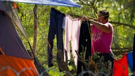 A person seeking asylum in the U.S. and waiting in Mexico, hangs laundry on a clothesline at a camp in Matamoros, Mexico,…