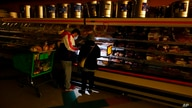 FILE - Customers use the light from a cell phone to look in the meat section of a grocery store Tuesday, Feb. 16, 2021, in…
