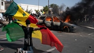 A demonstrator holds a Senegalese flag as he kneels in front of a burning car during protests against the arrest of opposition…