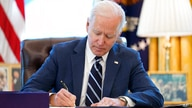 President Joe Biden signs the American Rescue Plan, a coronavirus relief package, in the Oval Office of the White House,…
