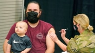 Isaac Hoffman holds his son Leo, 10 months, while receiving his Pfizer vaccine Thursday, March 25, 2021, in Spanish Fork, Utah…