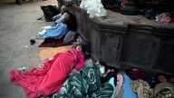 Migrants sleep under a gazebo at a park in the Mexican border city of Reynosa, Saturday, March 27, 2021. Dozens of migrants who…