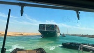 In this photo released by Suez Canal Authority, the Ever Given, a Panama-flagged cargo ship is accompanied.