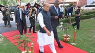 Indian Defense Minister Rajnath Singh walks with visiting U.S. Defense Secretary Lloyd Austin before reviewing an honor guard in New Delhi, March 20, 2021.
