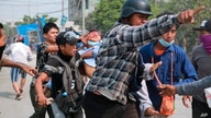 A man with a head injury is carried by fellow demonstrators during an anti-coup protest in Mandalay, Myanmar, March 22, 2021.