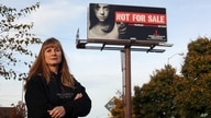 FILE - Dawn Stenberg, from the Junior League of Sioux Falls, stands near the group's anti-trafficking billboard in Sioux Falls, South Dakota, Oct. 27, 2015. About 50% of the women and girls falling prey to trafficking in the state are Native American.