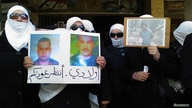 Women hold pictures of missing relatives as they protest against Syria's President Bashar al-Assad, in Daria, near Damascus, Jan. 19, 2012.