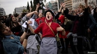 People dance and sing during a demonstration to mark International Women's Day in front of the parliament building in Athens, Greece.