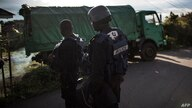 Cameroonian police officers look on as electoral officials leave on a truck with polling materials ahead of deployment in Buea…