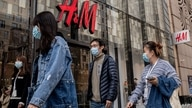 People walk past a store of Swedish clothing giant H&M in Beijing on March 25, 2021. (Photo by NICOLAS ASFOURI / AFP)