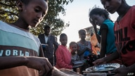 (FILES) In this file photo displaced children from Western Tigray wait at meal time to receive food outside a classroom in the…