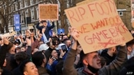 Football supporters demonstrate against the proposed European Super League outside of Stamford Bridge football stadium in…