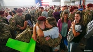 John Jacoby, a paratrooper with the 1st Brigade Combat Team, 82nd Airborne Division, hugs his girlfriend Emiliee Chance.