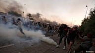 Demonstrators run as Iraqi security forces use tear gas during a protest after lifting of the curfew