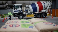 FILE PHOTO: A worker walks next to a cement mixer truck at a concrete plant of Mexican cement maker CEMEX in Monterrey, Mexico…